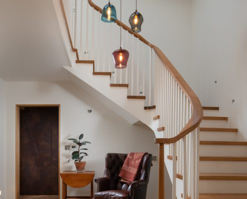 Entrance hall with a view of the stairs circling around the chandelier