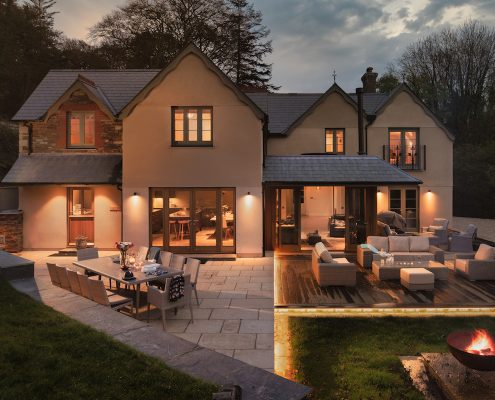 Rear view of the house at night with warm outdoor lighting and terraced seating areas